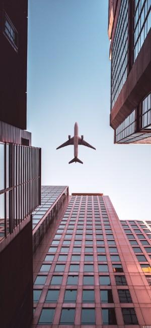 仰望高楼大厦上方的飞机
