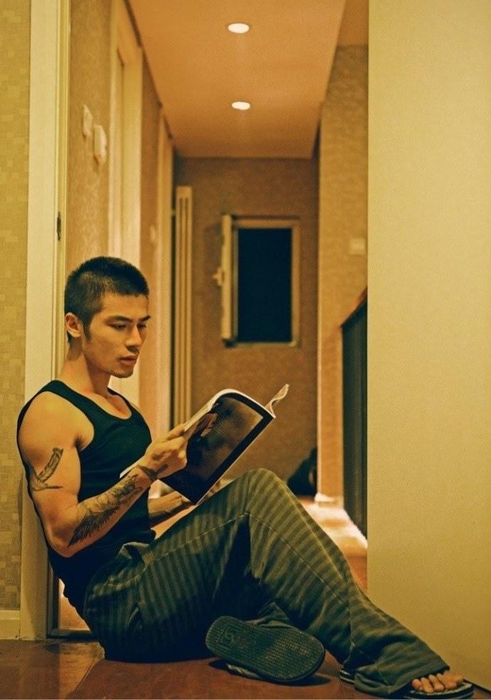 很文静的肌肉帅哥坐躺在地上看书